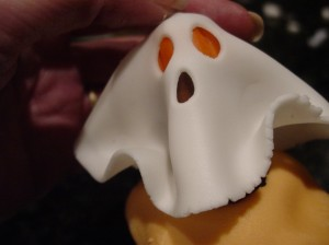 fondant ghost being placed on a cupcake