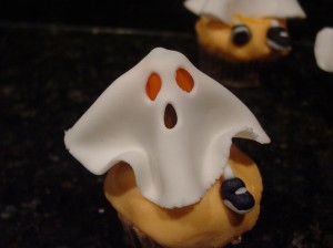 fondant ghost cupcake with leg and shoe dangling under the ghost sheet