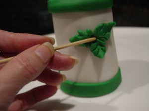 attaching fondant holly leaf's on tall cupcake using a wooden stick