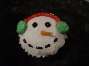 Christmas snowman cupcake with orange fondant nose and green earmuff