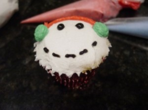 snowman cupcake with black pipng gel eyes and mouth
