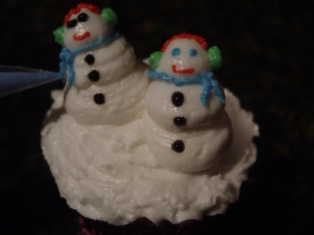 Snowman Cupcakes step 4 figure piping snowman eyes,nose,mouth,earmuffs and scarf