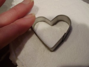 Heart Shaped Cookie Cutter Pressed into frozen icing for Santa face cupcake