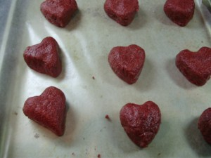 Heart shaped red velvet cake balls on lined baking sheet