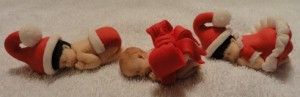 Christmas baby cupcake toppers in santa suites and bows